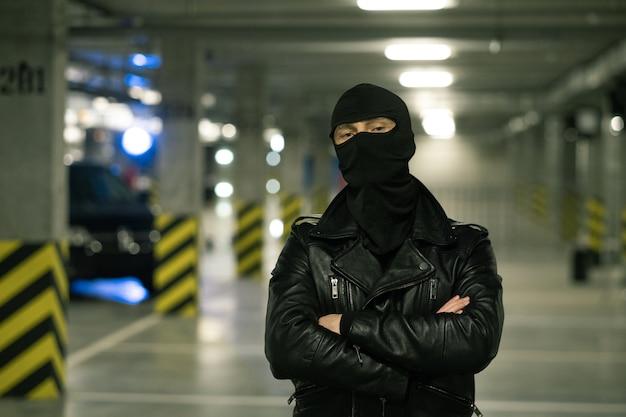 Zeitgenössischer verbrecher in schwarzer lederjacke und sturmhaube auf kopfkreuzungsarmen durch brust mit parkplatz auf hintergrund