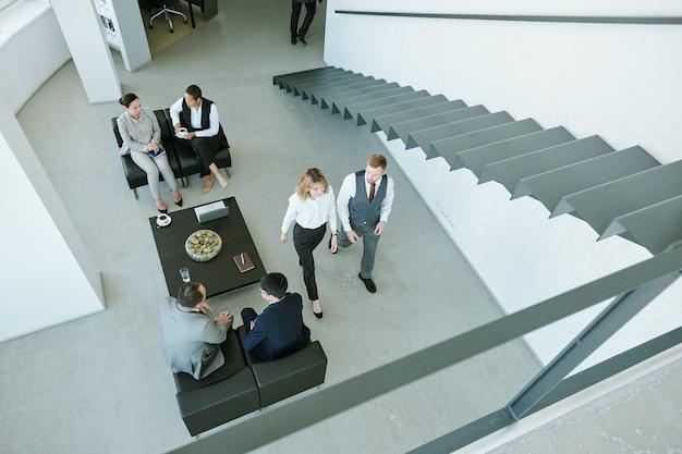 Zeitgenössisches büro mit langer schmaler treppe und drei kleinen gruppen von geschäftsleuten, die über arbeitspunkte in der pause diskutieren