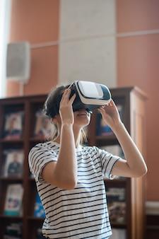 Zeitgenössisches junges mädchen mit vr-headset, das virtuelle anzeige beim betrachten des 3d-films in der hochschulbibliothek betrachtet