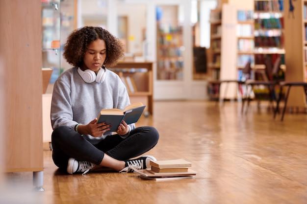 Zeitgenössisches mädchen in röhrenjeans und grauem sweatshirt-lesebuch beim sitzen auf dem boden in der hochschulbibliothek