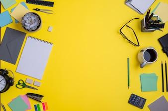 Zeitgenössischer Arbeitsplatz mit Lieferungen auf gelbem Hintergrund
