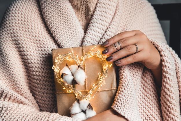 Zeitgeschenke - geschenkbox in der hand mädchen. geschenk in den händen einer frau. plaid, baumwolle, maniküre. valentinstag