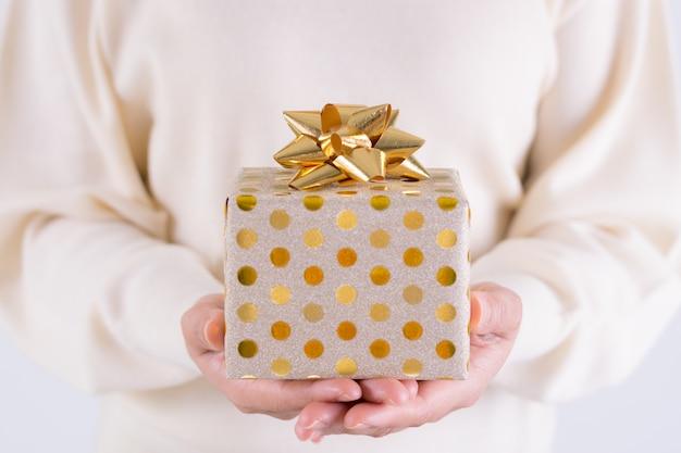 Zeitgeschenkkonzept - geschenkbox mit mädchen des goldbogens in der hand. weihnachts- oder verpackentagskonzept. geburtstag-konzept.