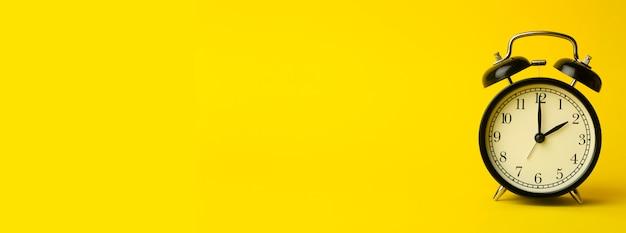 Zeithintergrundkonzept. klassischer wecker der weinlese auf gelbem leerem hintergrund. zeitmanagement-konzept