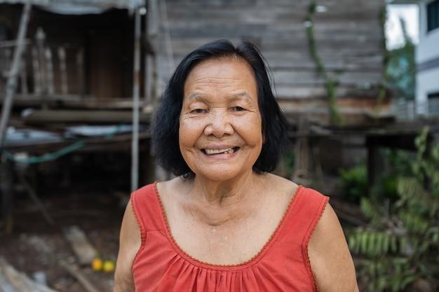 Zeitlupe der älteren thailändischen frau im ärmellosen kragen mit rundem hals, der im alten hölzernen haus lacht