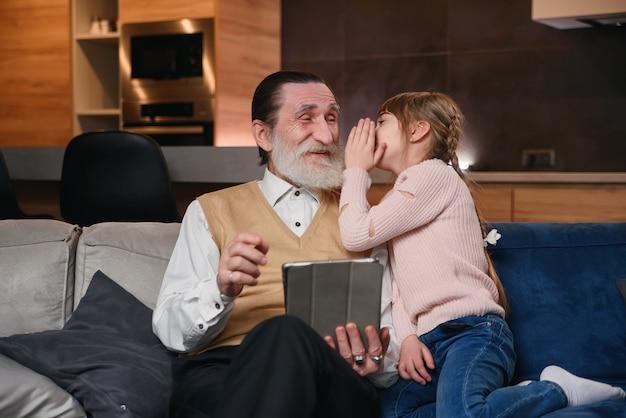 Zeitlupe des niedlichen freudigen 12-jährigen mädchens mit lustigen zöpfen, die auf opas ohr ihr geheimnis flüstern, während sie zu hause zusammen auf dem sofa sitzen