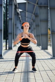 Zeitlupe des widerstandsband-fitnessmädchens in kopfhörern, die kniebeugenübungen mit stoffbeuteband während ihres sporttrainings auf speziellem sportplatz machen