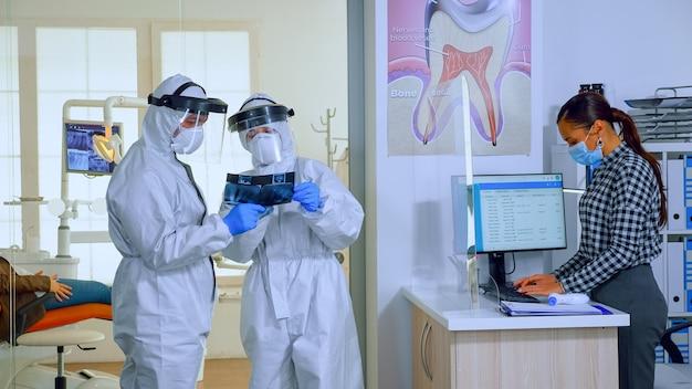 Zeitlupe von stomatologischen ärzten mit gesamtbetrachtung des röntgenbildes im wartebereich, planung einer operation während der globalen pandemie, während ältere patienten das sitzen auf stühlen diskutieren, um abstand zu halten.