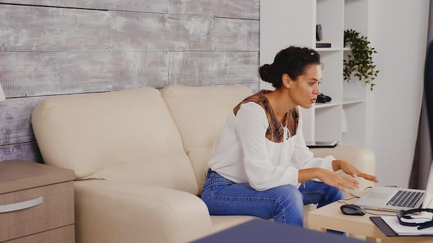 Zeitlupenaufnahme einer frau, die während eines videoanrufs winkt, während sie von zu hause aus arbeitet.