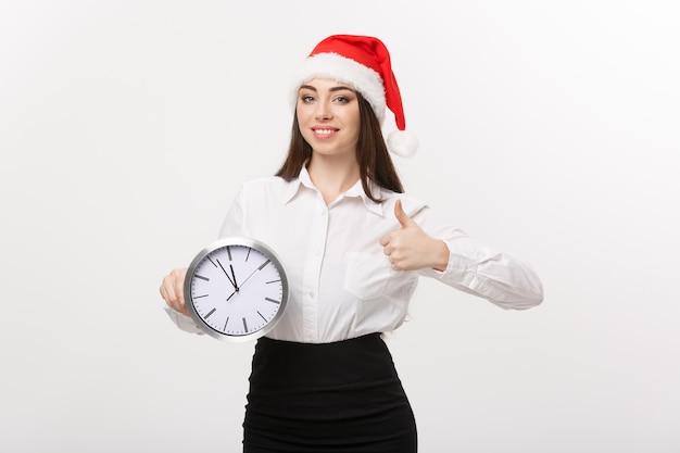 Zeitmanagement-konzept - junge geschäftsfrau mit weihnachtsmütze, die eine uhr hält und schlag oben über weißer wand zeigt.