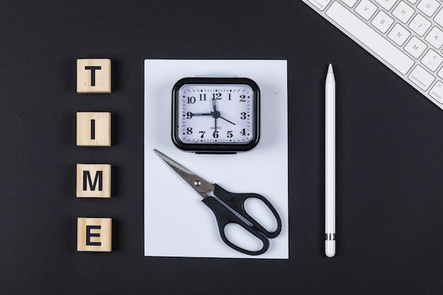 Zeitmanagement-konzept mit holzklötzen, schere, uhr, bleistift, papier, tastatur auf schwarzem hintergrund draufsicht. horizontales bild
