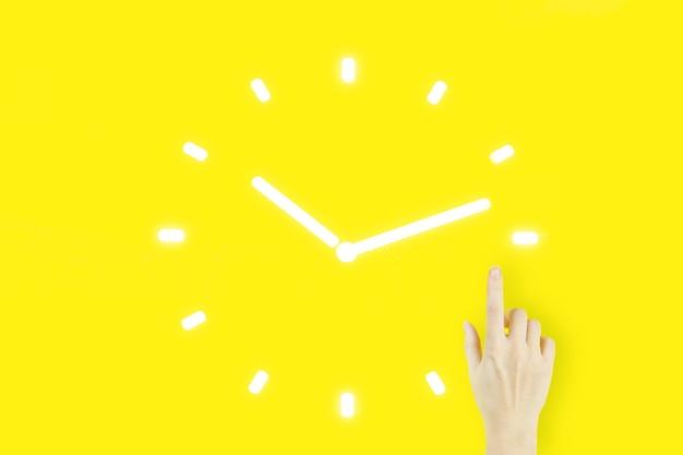 Zeitmanagement-projekteffizienzstrategie ziele business-technologie-internet-konzept. handfinger der jungen frau, der mit gelbem hintergrund der hologrammuhr n zeigt.