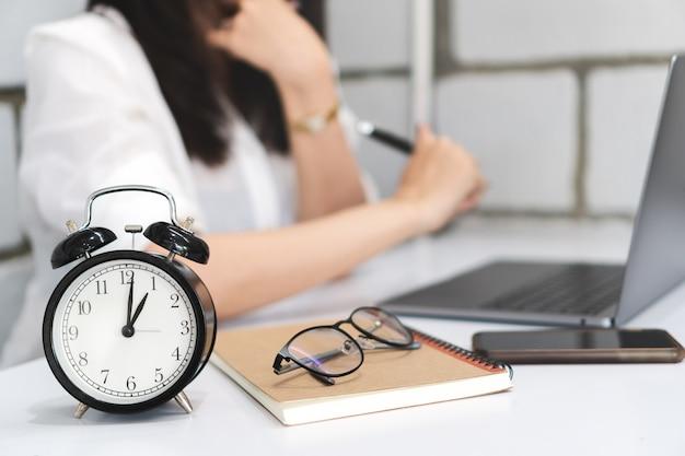 Zeitmanagement, schwarzer wecker mit unscharfer geschäftsfrau arbeitet mit laptop.