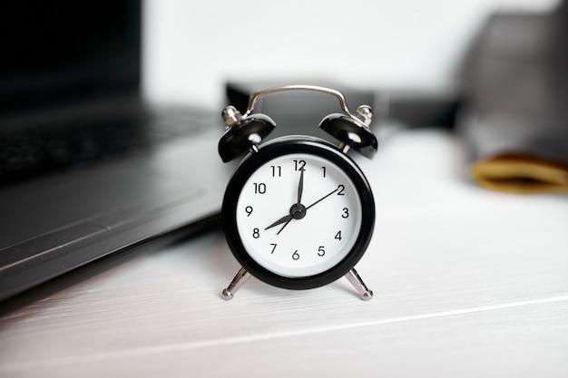 Zeitmanagementkonzept, büroarbeitsplatz, notizbuch, computer, laptop und schwarzer wecker auf weißem hölzernem schreibtisch, kopienraum