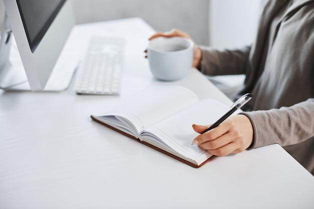 Zeitplan hilft, meinen tag aufrechtzuerhalten. kurzer schuss der frau, die vor computer arbeitet, in notizbuch schreibt und kaffee trinkt. die geschäftsfrau plant tagsüber ihr treffen