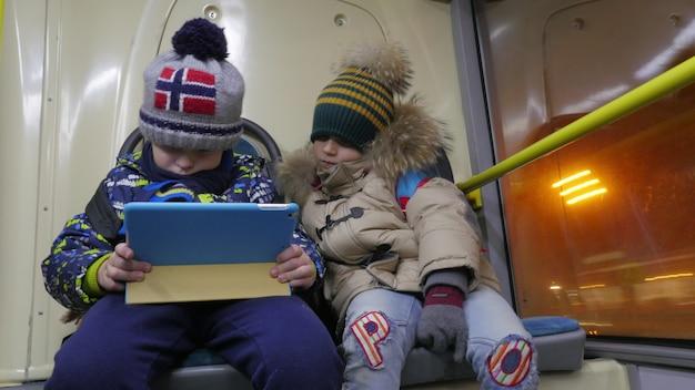 Zeitraffer von zwei jungen mit tablet-computer im oberleitungsbus