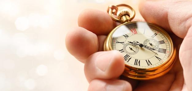 Zeitsymbol-konzept. retro-goldtaschenuhr in der hand.