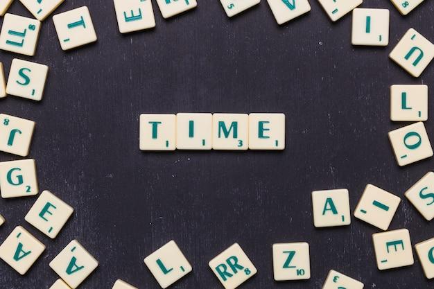 Zeittext auf scrabble-buchstaben auf schwarzem hintergrund
