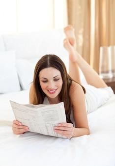 Zeitung der eleganten frau lese, die auf bett liegt