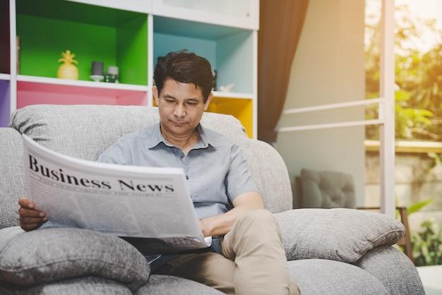 Zeitung des älteren mannes lesung business news auf sofa im wohnzimmer zu hause