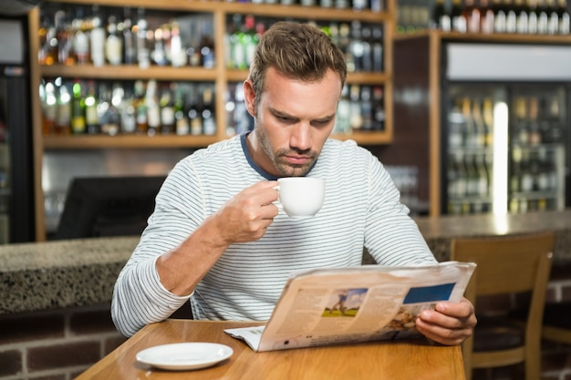Zeitung des gutaussehenden mannes leseund einen kaffee trinkend
