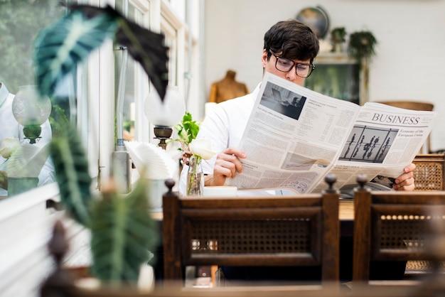 Zeitung des jungen mannes morgens lesend