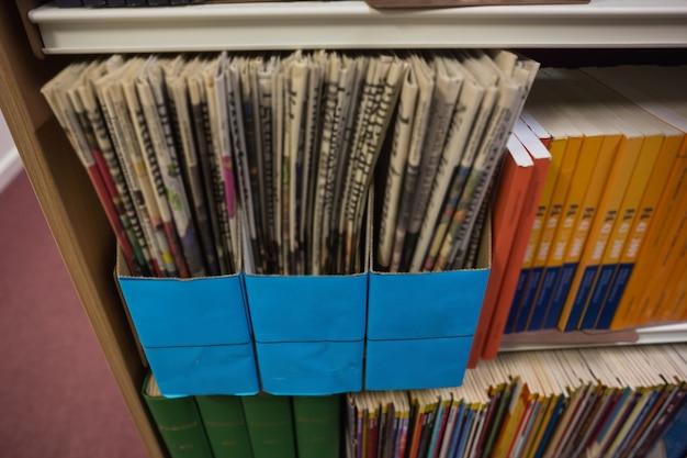 Zeitungen auf bücherregal in der bibliothek