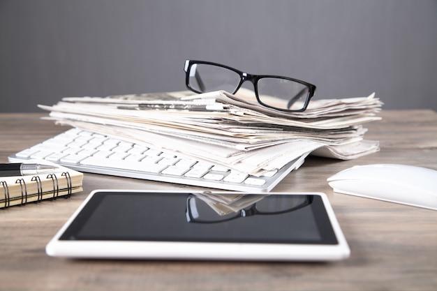 Zeitungen, computertastatur, brillen auf dem holztisch.