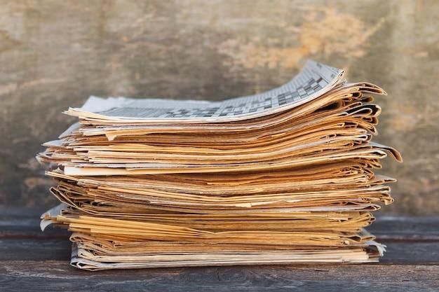 Zeitungen und zeitschriften auf altem holztisch.