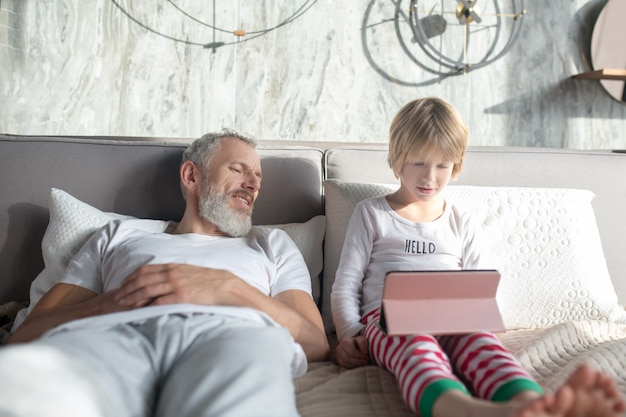 Zeitvertreib, ruhe. grauhaariger erwachsener interessierter mann, der liegt und intensiv kind mit tablette sieht, die auf bett sitzt