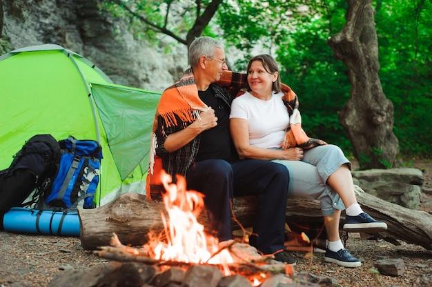Zelt camping paar romantisch sitzen am lagerfeuer nacht landschaft.