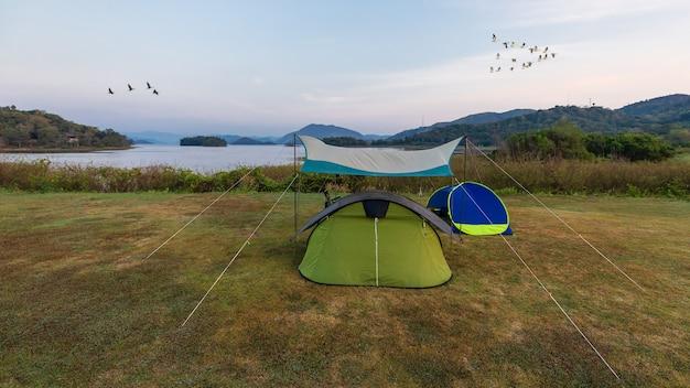 Zelt neben dem großen see mit schöner landschaftsansicht und einer gruppe von vögeln, die im blauen himmel fliegen. idee für ein erholsames leben in ruhe und gelassenheit im freien.