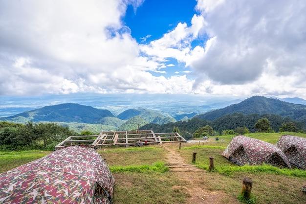 Zelte beim kampieren unter wiese mit schöner landschaft in den bergen unter himmel und clou