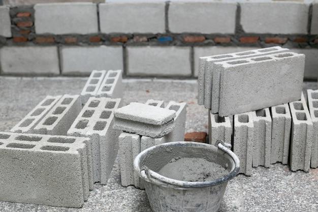 Zement oder mörser, zementpulver mit einer kelle setzte auf den ziegelstein bei den bauarbeiten.