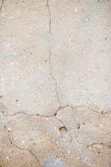 Zementwand mit kieseln und sprung