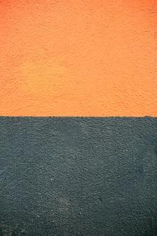 Zementwandhintergrund der schwarzen und orange textur