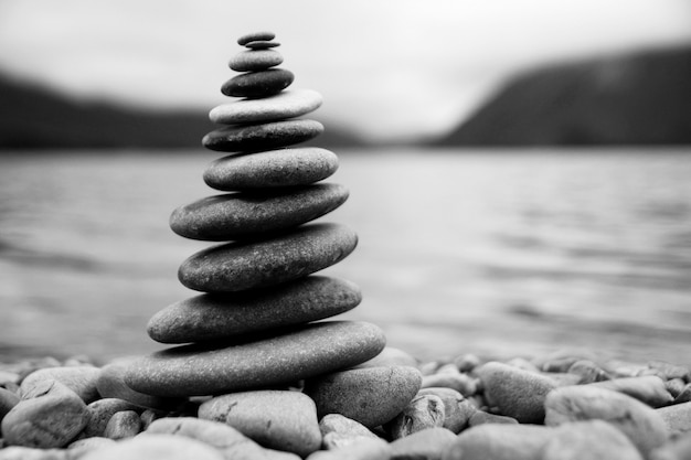 Zen balancieren von kieselsteinen neben einem nebligen see