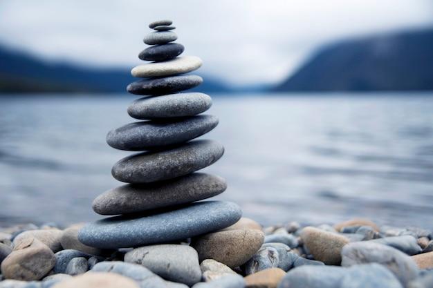 Zen balancing kieselsteine neben einem nebligen see.