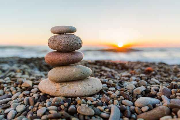 Zen-basaltsteine auf sonnenuntergangstrandhintergrund