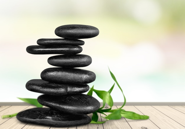Zen-basaltsteine und -blätter im hintergrund