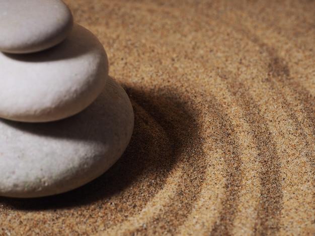 Zen garten. pyramiden aus weißen und grauen zen-steinen auf dem weißen sand mit abstrakten wellenzeichnungen.