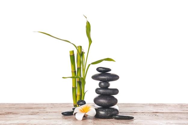 Zen steine, blume und bambus auf tisch gegen weiß