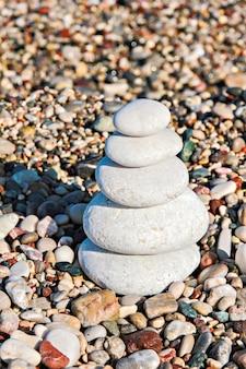 Zen-steine, die am strand gegen einen kies gestapelt sind