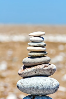 Zen-steine, die am strand gegen sand und himmel gestapelt sind