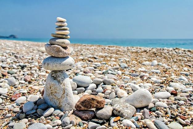 Zen-steine gestapelt am strand vor blauem himmel und meer mit kopierraum