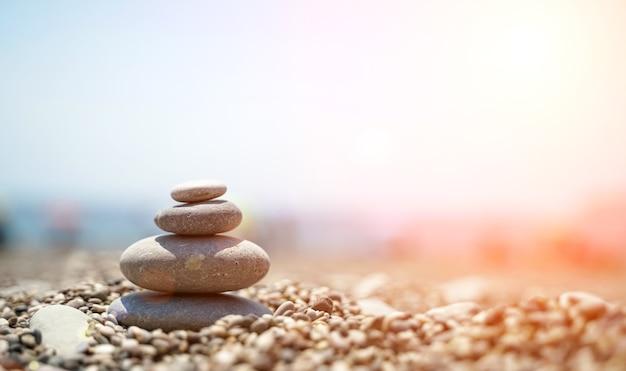 Zen-steine sind der hintergrund einer pyramide aus kieselsteinen vor dem hintergrund des himmels, des meeres und des strandes...