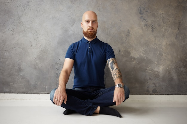 Zen-, yoga- und meditationskonzept. isolierter schuss des gutaussehenden bärtigen kerls mit rasiertem kopf, der auf holzboden mit gekreuzten beinen sitzt, ruhigen gesichtsausdruck hat und mit geöffneten augen meditiert