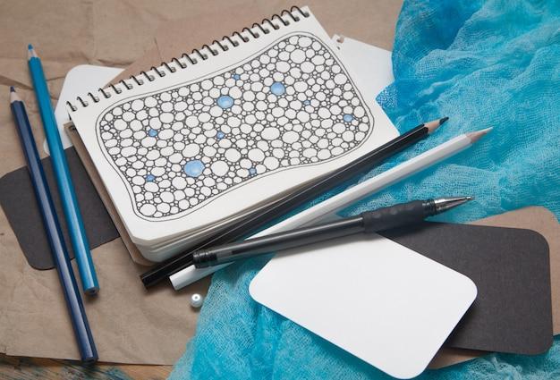 Zentangle-artzeichnungen in einem notizbuch, ein dunkelbrauner hölzerner hintergrund, gekritzel