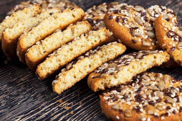 Zerbrochene halb leckere und frische haferflocken-weizen-kekse, bestreut mit nüssen und samen verschiedener arten