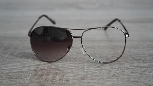 Zerbrochene sonnenbrille ohne glas auf grauem holz